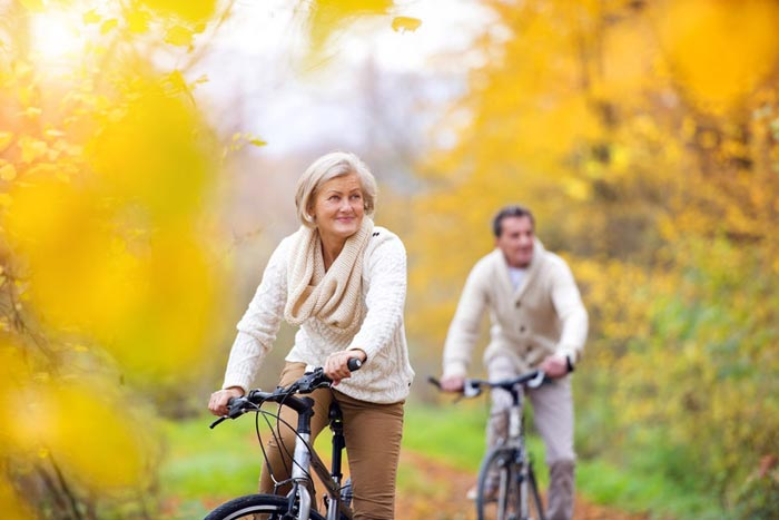Retirement Planning Service - Active seniors having walk with bike in autumn nature